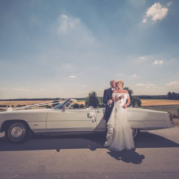 Bride and Groom with wedding car at Hazlewood Castle